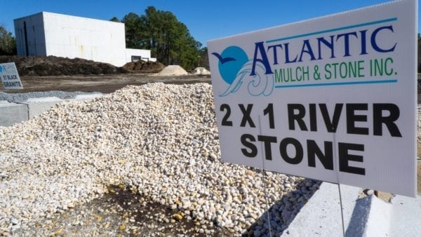 mound of 2x1 white River Stone with Atlantic Mulch & Stone sign to the right