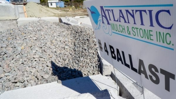 mound of #4 ballast with Atlantic Mulch & Stone sign to the right