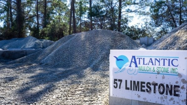 mound of 57 limestone with Atlantic Mulch & Stone sign on right