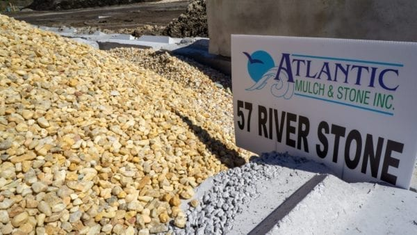 mound of 57 river stone with Atlantic Mulch & Stone sign to the right