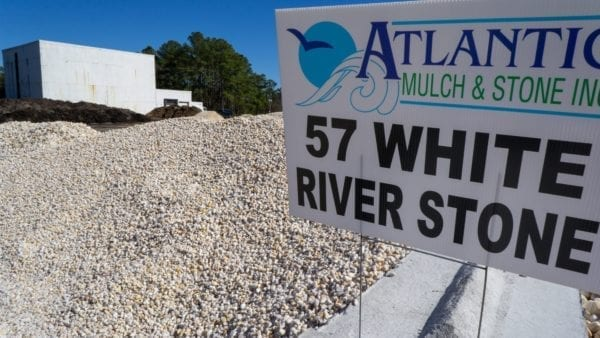 mound of 57 white river stone with Atlantic Mulch & Stone sign to the right