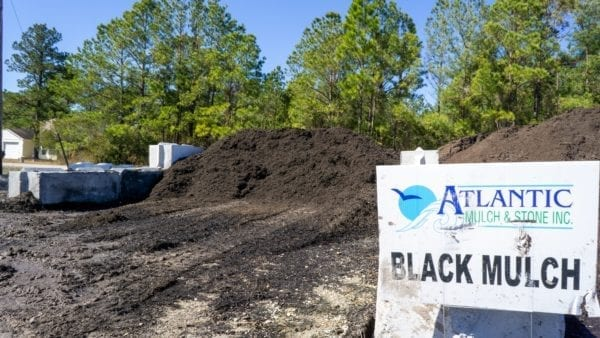 mound of black mulch with Atlantic Mulch & Stone sign on the right