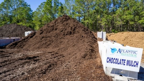 mound of chocolate mulch with Atlantic Mulch & Stone sign on the right