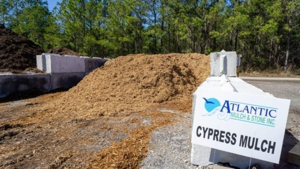 cypress mulch mound with Atlantic Mulch & Stone sign on the right
