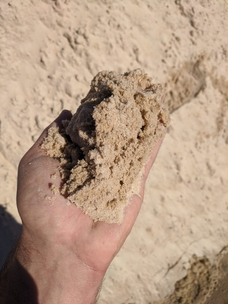 mortar sand in hand for scale and detail