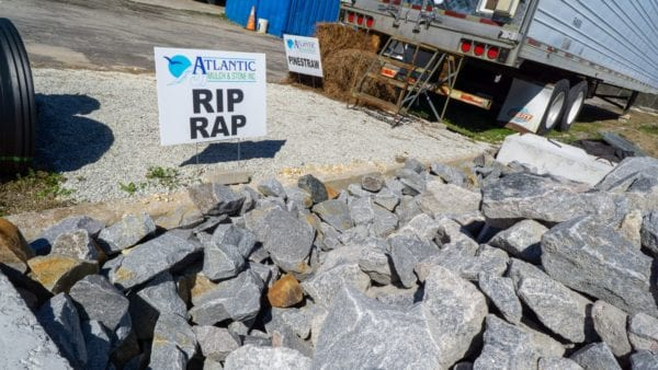 mound of rip rap with Atlantic Mulch & Stone sign on the left
