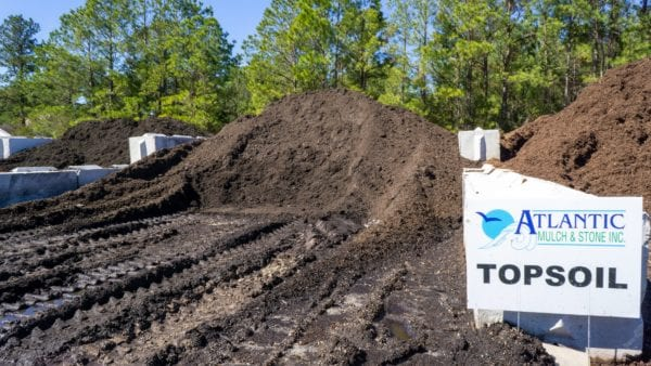 mound of dark topsoil with Atlantic Mulch & Stone sign to the right